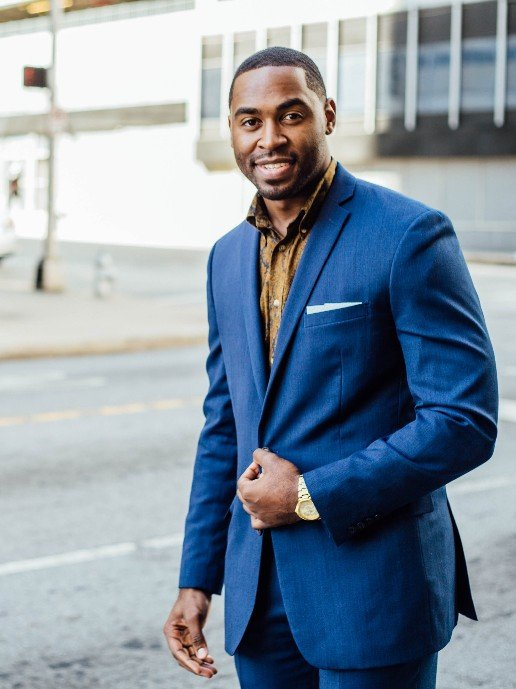 Black business man smiling in a blue suit